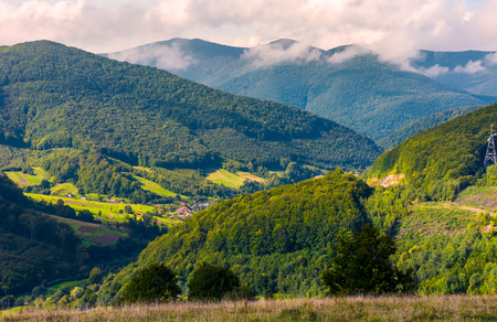 village in the valley of Carpathian mountains. lovely countryside scenery in early autumn with clouds rising from the forest on the distant ridge Stock Photo