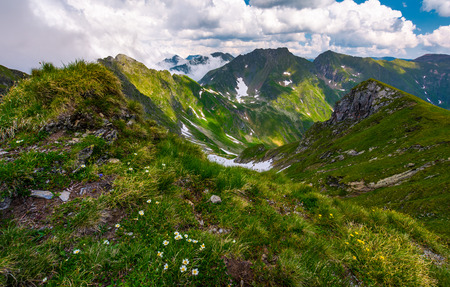 gorgeous summer landscape in mountains. grassy slope with flowers and rocky cliffs with some snow. beautiful cloudy sky Stock Photo - 93232180