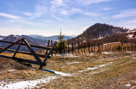 언덕에 깨진 된 나무 울타리입니다. 봄이오고있다. 밝은 하루에 풍 화 잔디와 슬로프에 일부 눈이 아름 다운 산악 풍경 스톡 콘텐츠 - 93074835