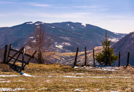언덕에 깨진 된 나무 울타리입니다. 봄이오고있다. 밝은 하루에 풍 화 잔디와 슬로프에 일부 눈이 아름 다운 산악 풍경