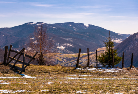 broken wooden fence on hillside. springtime is coming. beautiful mountainous landscape with some snow on slopes with weathered grass on a bright day