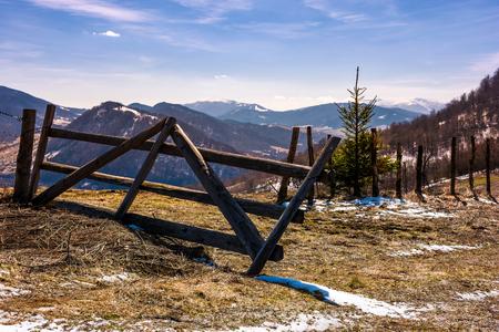 丘の斜面に壊れた木製のフェンス。春が来ている。明るい日に風化した草と斜面にいくつかの雪と美しい山岳風景