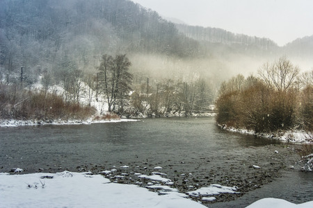 冬の田園地帯の川に霧が暗い曇り天気 写真素材