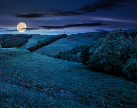lovely countryside with grassy hills at night in full moon light. beautiful nature of Carpathian mountains in springtime Stock Photo