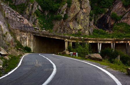 tunnel on Transfagarasan road of Romania. dangerous transportation scenery among the rocky cliffs in high Carpathian mountains in summer morning.  Stock Photo