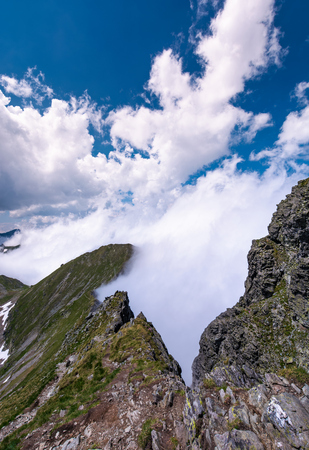 Beautiful clouds-cape over the cliffs of Fagarasan mountain ridge. lovely nature background on a summer day