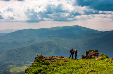 tourists stand on cliff enjoying the view. gorgeous view of magnificent Polonina Runa ridge from the hills of Pikui mountain. Location Ukrainian Carpathians