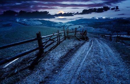 hek langs de landweg in landelijk gebied. mooi agrarisch landschap in de Karpaten. grasvelden op heuvel in de lente 's nachts in volle maanlicht. Locatie Volovets, Oekraïne