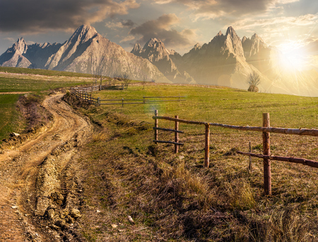 road through rural fields in mountainous area. composite imagery of agricultural countryside in springtime at sunset. wooden fence along the grassy fields on hillside Stock Photo