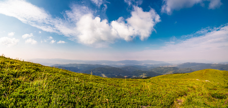 山岳風景の美しいパノラマ。山の尾根の芝生の斜面にいくつかの雲と青い空。素敵な夏の天気 写真素材