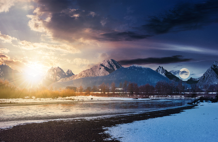 day and night time change over the river. composite winter landscape in mountainous area.