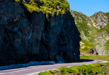 road under the cliff in high mountains. transportation background with dangerous aspect