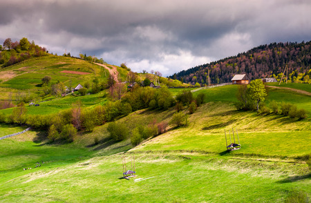 wooden fences of rural area on grassy hillsides. lovely rural landscape of mountainous village in springtime