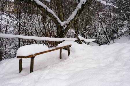 houten bank in besneeuwde buitenshuis. mooi winterlandschap in park