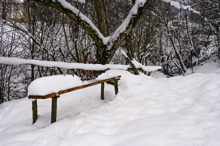 wooden bench in snowy outdoors. lovely winter scenery in park Stock Photo
