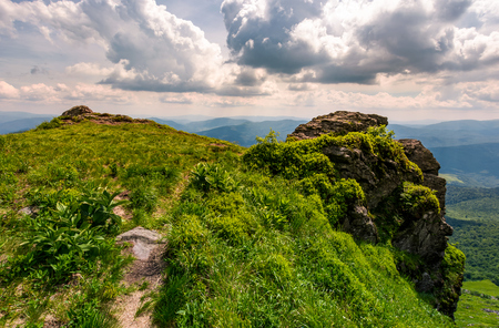 path to the edge of a rocky cliff. beautiful landscape of Carpathian mountains on a cloudy summer day