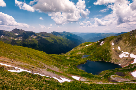 beautiful summer landscape of Fagaras mountains. stunning view from the top of a hill under the sky with clouds. lovely glacier on grassy slope over the deep long valley of Southern Carpathians