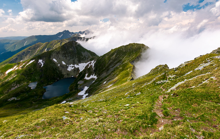 tourist foot path along the mountain ridge. beautiful landscape with lake and rising clouds Stock Photo