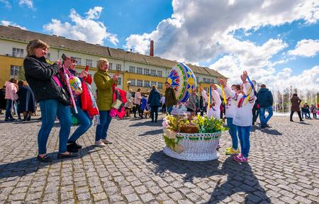 Uzhgorod, Ukraine - April 07, 2017: Celebrating Orthodox Easter in Uzhgorod on the Narodna square. women take photos of children near the big basket with flowers near huge egg on warm springtime day. Editorial
