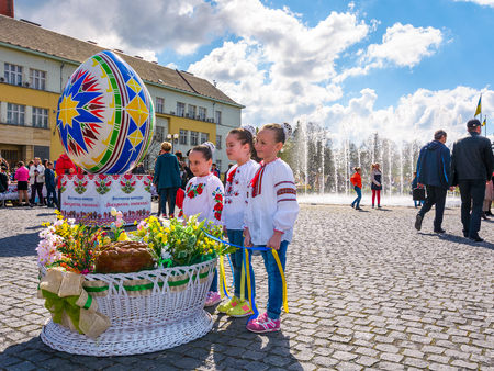 Uzhgorod, Ukraine - April 07, 2017: Celebrating Orthodox Easter in Uzhgorod on the Narodna square. Huge egg near the fountain on a warm springtime day. kids near the big basket with flowers