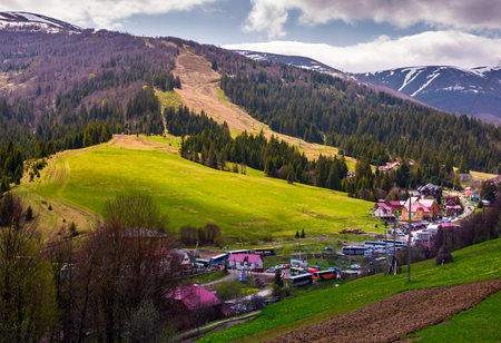 Pylypets, Ukraine: Tourist buses in Pylypets resort village. beautiful springtime landscape in Carpathian mountains