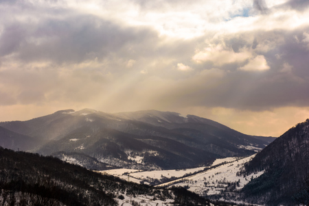 beam of light through cloudy sky over the mountain. lovely winter landscape