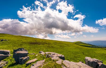 잔디 언덕 위에 화려한 cloudscape입니다. 여름철에 아름 다운 산 풍경