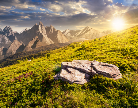 composite of meadow in rocky mountains at sunset. beautiful unrealistic landscape in summertime  Stock Photo
