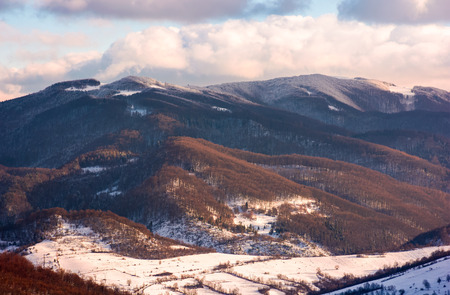 lovely countryside in winter afternoon. beautiful mountainous area with forested hills with snowy tops Stock Photo
