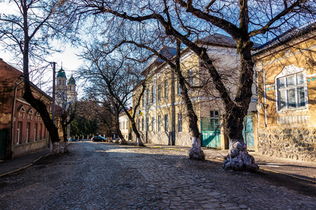 street of old town in sunny spring day. cobblestone road, beautiful architecture and old Cathedral in the distance Stock Photo