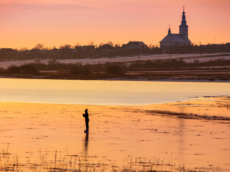 silhouette  person skating on the frozen lake in evening. beautiful winter countryside scenery. village and church in a far distance