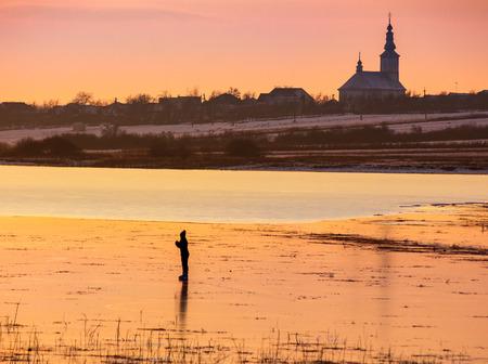 Silhouette personne patiner sur le lac gelé en soirée. paysage de campagne d'hiver magnifique. village et église au loin Banque d'images - 94394035