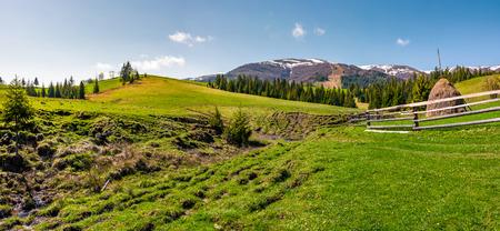 農村地域の草原のパノラマ。雪の頂上と森と山の尾根と豪華な春の風景。小川の近くのフェンスの後ろの干し草の山 写真素材