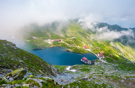 Balea lake view from above. beautiful landscape in Fagaras mountains with rising cloud on summer day