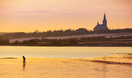 Silhouette personne patiner sur le lac gelé en soirée. paysage de campagne d'hiver magnifique. village et église au loin Banque d'images - 94392603