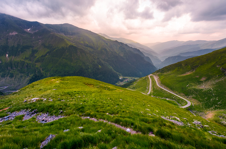 valley in Fagarasan mountains in afternoon. beautiful nature scenery on a cloudy summer day. view from the grassy hillside with footpath. part of Transfagarasan road is visible on the right slope Stock Photo
