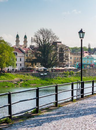 Uzhgorod, Ukraine - April 13, 2016: beautiful cityscape of the old central part of a town on the river Uzh in springtime, viewed from the Kyiv embankment with metal fence and lanterns Stock Photo - 94698109