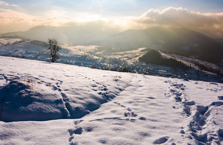 snowy slope in mountainous countryside. gorgeous weather with clouds over the mountain ridge.  Stock Photo