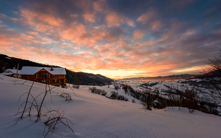 winter sunrise with red clouds in the village. beautiful winter countryside in mountains with snowy slopes Stock Photo