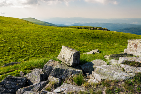 rocks on grassy meadow on top of a hill. beautiful summer scenery in mountains Stock Photo