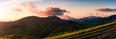 夕暮れ時の山々のパノラマ。春の紫色の雲と緑の丘と美しい風景