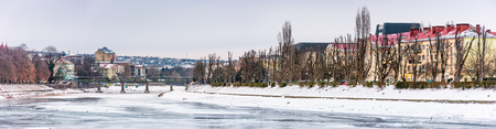 panorama of winter cityscape on the river Uzh. lovely travel background with Kyiv embankment, pedestrian bridge and some architecture of central part of old town Uzhgorod Editorial