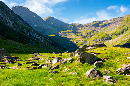lovely scenery of Transfagarasan road in valley. rocks on grassy meadow and slopes. half of the valley in shade of mountain ridge Stock Photo