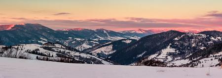 冬の夜明けに山の尾根のパノラマ。雪の中の森林の丘と美しい風景。赤い日差しに照らされた空と山頂の雲 写真素材