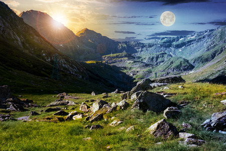 time change concept in Transfagarasan valley. rocks on grassy meadow and slopes lit by sun and moon simultaneously. half of the valley in shade of mountain ridge Foto de archivo