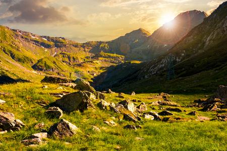prachtig landschap van Transfagarasan weg in vallei bij zonsondergang. rotsen op met gras begroeide weide en hellingen. helft van de vallei in de schaduw van bergrug