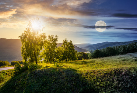 time change concept over the trees on grassy hill in mountains. lovely nature scenery with sun and moon
