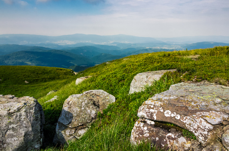 grassy slope of a hill with huge boulders. beautiful landscape of Polonina Runa ridge on a cloudy summer day