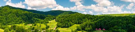 夏の山岳農村地域のパノラマ。谷の森の丘と村の美しい風景。曇り空の下の草原の農地 写真素材