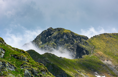 mountain peak over the cliff and clouds. beautiful summer scenery of Fagaras mountains Stock Photo